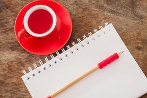 röd mugg med öppen anteckningsbok foto