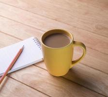 kaffekopp med anteckningsböcker och pennor. foto