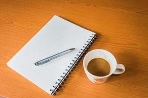 anteckningsbok och kaffe på träbakgrund foto