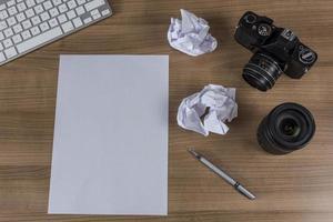 skrivbord med kamera och tomt ark foto