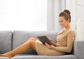 ung kvinna sitter på soffan och använder tablet pc foto