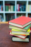 hög med färgade böcker på trä skrivbord foto