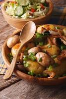 potatis med svamp närbild i skål och sallad. vertikal