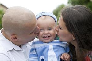 vacker lycklig ung familj med baby foto