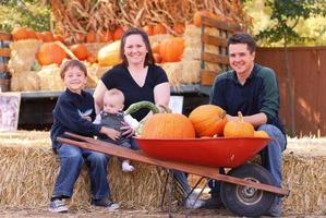 familj som sitter på höstack med pumpor foto