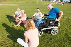 handikappad man med familjen utanför. foto