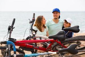 familj med cyklar på stranden foto