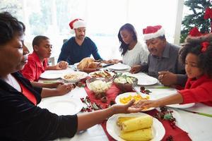 familj med flera generationer som ber före julmåltid foto