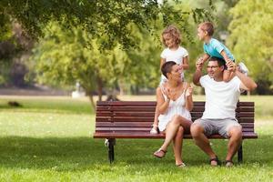ung familj som har kul i parken foto