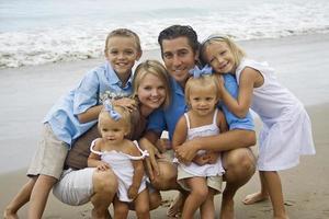 familj poserar leende på stranden
