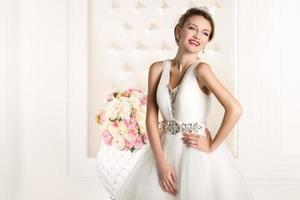 underbar brud med vit klänning med blommabukett foto
