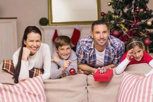 lycklig familj lutad på soffan foto