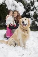 familj med en hund på snön foto