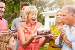 multi generation familj firar födelsedag i trädgården foto