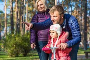 ung familj i höstlig skog som pekar