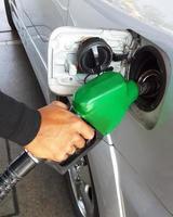 närbild av mannen som pumpar bensinbränsle i bilen foto