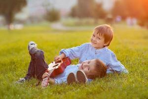 två bedårande pojkar, sitter på gräset och spelar gitarr foto