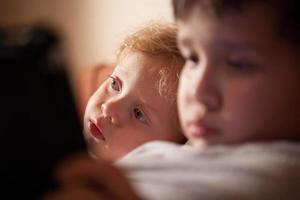 sött barn kopplar av med sin bror foto