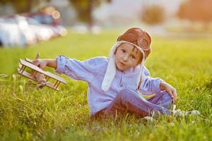 söt pojke, leker med flygplanet vid solnedgången i parken foto