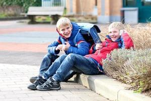 två pojkar med smartphone efter skolan foto