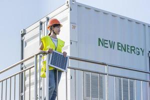 ingenjör som håller solpanel bredvid järnräcke foto