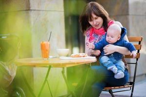 ung mamma med sin lilla son som äter frukost