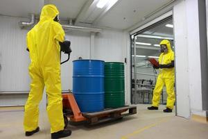 två arbetare som arbetar med fat kemikalier i fabriken foto