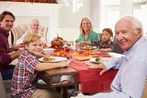 familj med morföräldrar och njuter av tacksägelse måltid vid bordet foto
