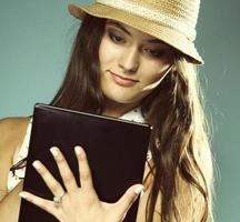 vacker glad tjej i sommarhatt med pekplatta e-läsare ipad foto