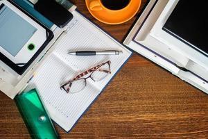 bok, anteckningsbok, glasögon på skrivbordet. foto