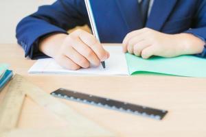 skrivbordsbakgrund av student som sitter vid skrivbordet för klassarbete foto
