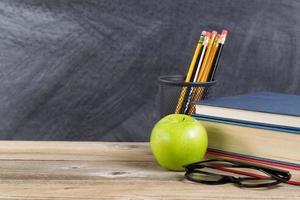 gamla trä skrivbord med grönt äpple och läsmaterial foto