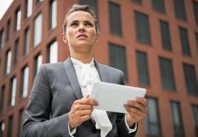 affärskvinna med TabletPC framför kontorsbyggnaden foto