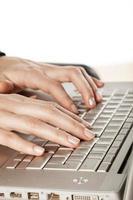 kvinnors fingrar som rör vid tangentbordet på den bärbara datorn foto