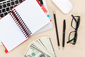 kontorsbord med pc, leveranser och pengar kontanter