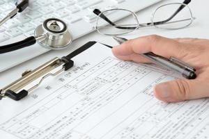 läkare som skriver läkarundersökning foto