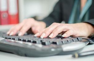 händer att skriva på ett tangentbord foto
