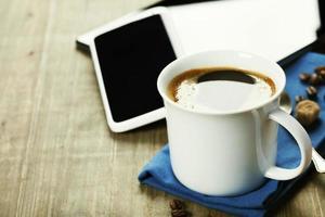 kopp kaffe med digital tablet PC och smart telefon foto