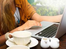 kvinnan skriver bärbar dator i ett kafé foto