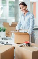 affärskvinna som packar upp på sitt nya kontor foto