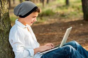 tonåring pojke som umgås på bärbar dator utomhus. foto