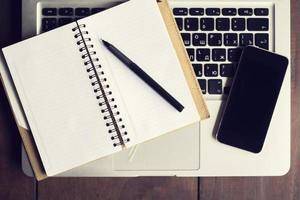 öppen anteckningsbok, mobiltelefon och bärbar dator foto