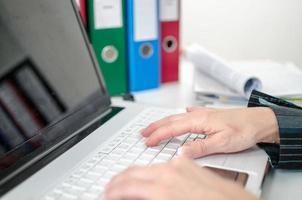 händer att skriva på ett laptop tangentbord foto