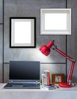 modernt skrivbord med bärbar dator, lampa och tomma bildramar foto
