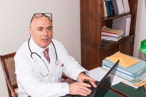 läkare i sin studio vid skrivbordet, på pc, med glasögon. foto