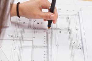 kvinna arkitekt ritning på utskrifter byggprojekt foto