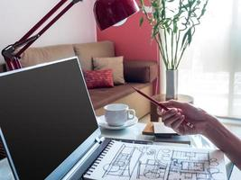 designer som arbetar med bärbar dator och arkitektonisk ritning i modern arbetsyta foto