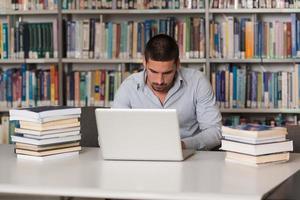 ung man använder bärbar dator i biblioteket foto