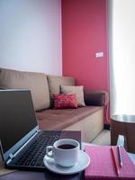 bärbar dator med kaffekopp på soffan i modernt vardagsrum foto