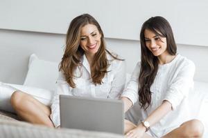 två vackra kvinnor som använder en anteckningsbok i sängen foto